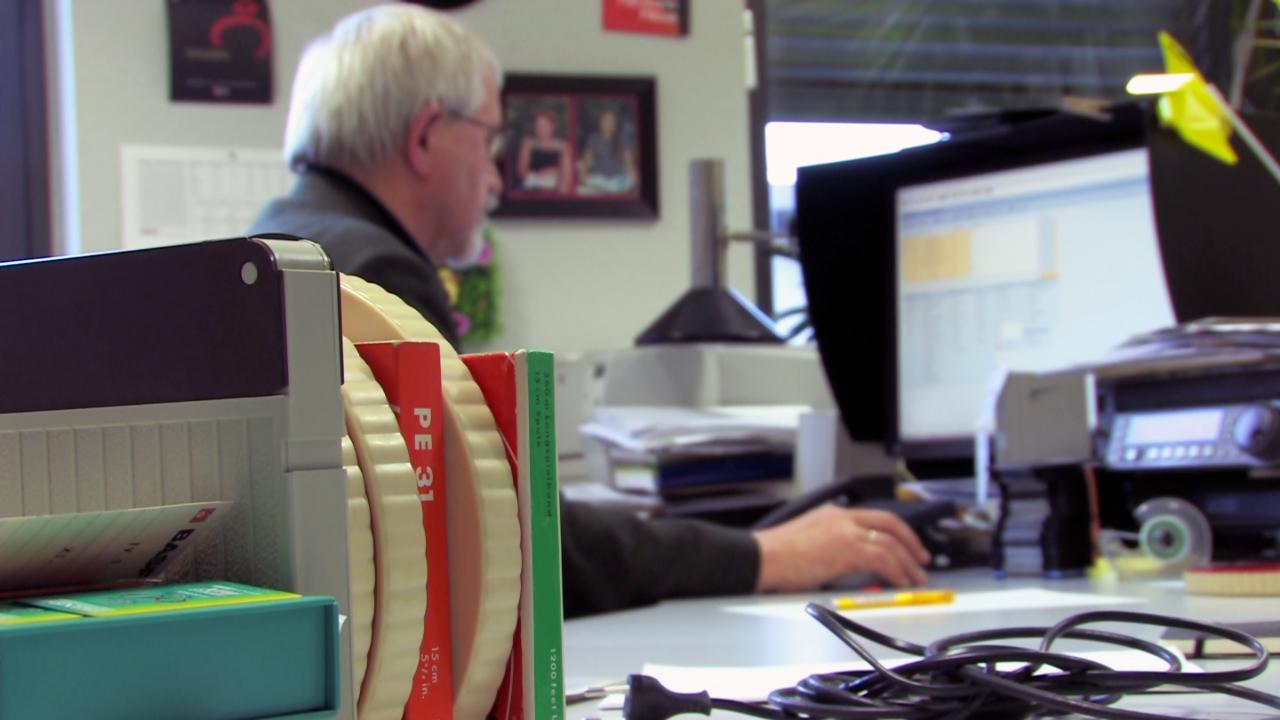 Gestapelte Filmrollen: Hans Hauptstock in seinem Büro