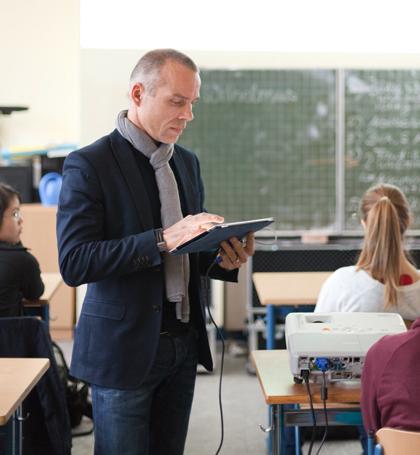 André Spang mit iPad im Klassenraum.